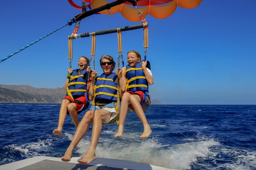 dad and kids are playing parasailing