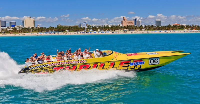 visitors sit on yellow speed boat tour miami