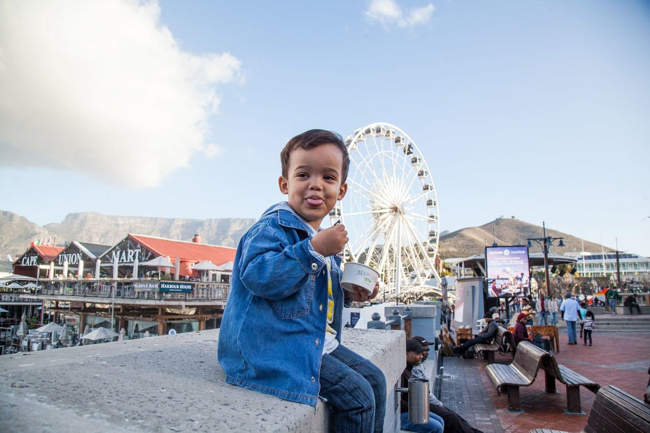 a boy sits in front of the Cape Wheel in Cape Town