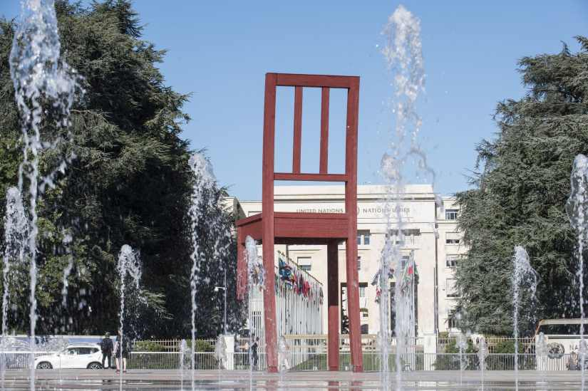 a broken chair in font of the main gate of United Nations Office at Geneva