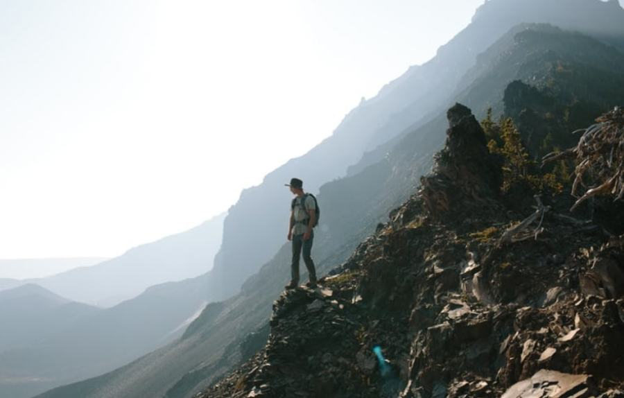 man hiking in the mountains with a tripod