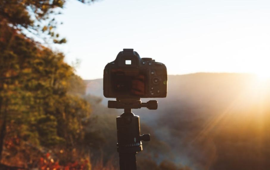 tripod attached to a camera with sun rise