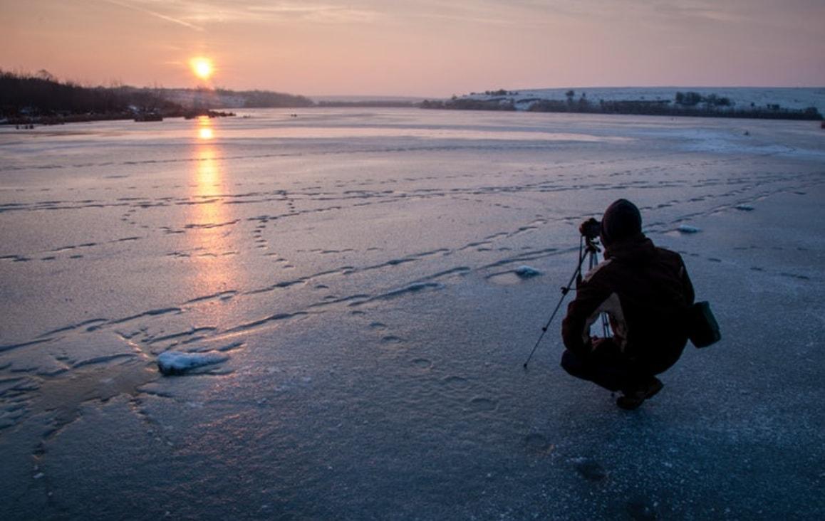 man using tripod on ice