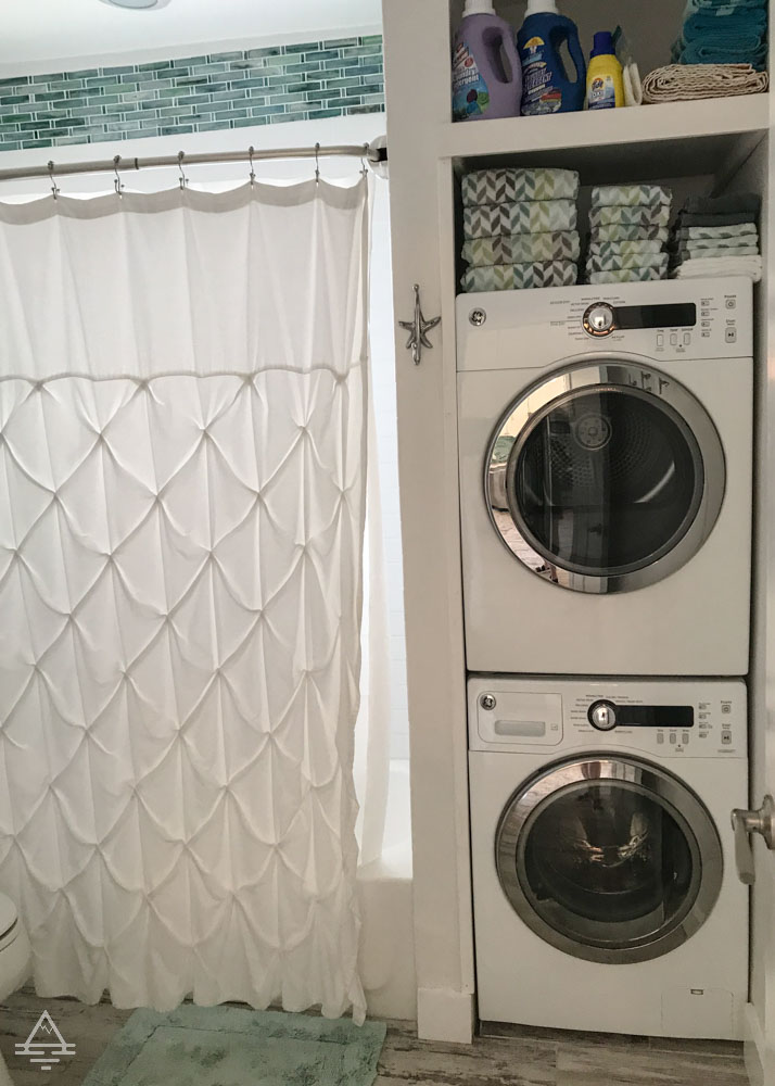 Stackable washer and dryer next to bathtub