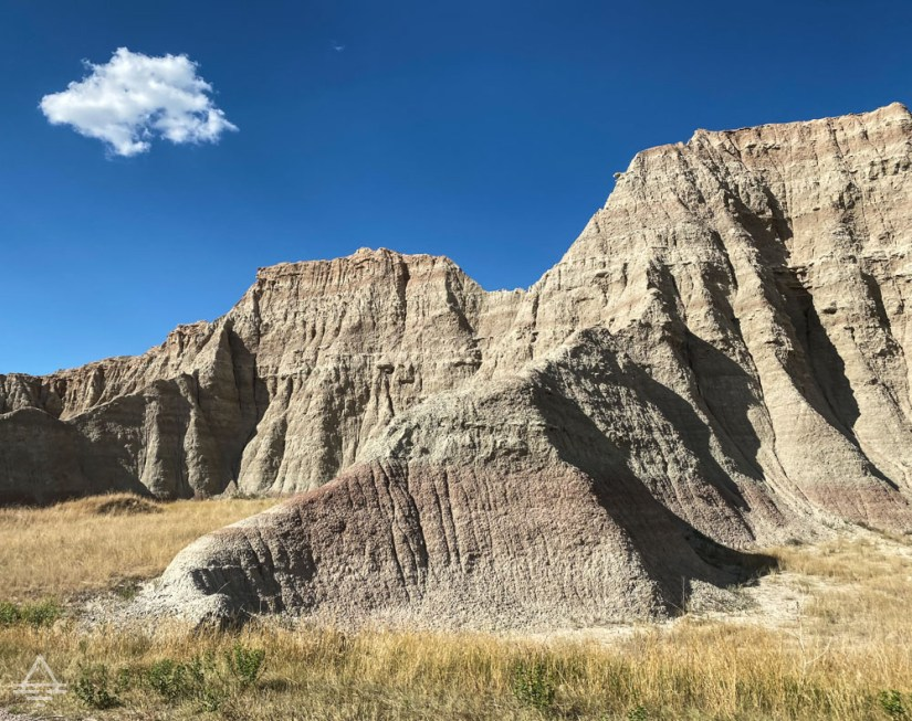 Badlands rock formations against a blue sky with one white cloud