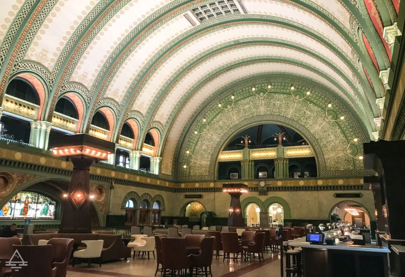 Inside the Great Hall at Union Station in St Louis with a high decorated ceiling and tables and chairs.