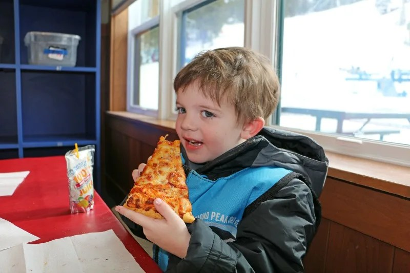 Child eating pizza lunch at ski school at Diamond Peak Resort.
