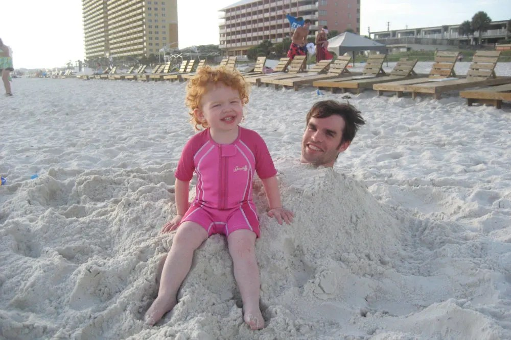 Florida Panhandle Emerald Coast Beaches - Child Burying Dad in Sand