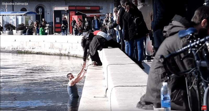 Jedan od vaterpolista je skočio u more, prolaznici mu pomažu da izađe (foto: printscreen Youtube Slobodna Dalmacija)