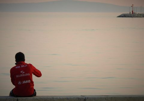 Usamljeni mladić sjedi na praznoj rivi (foto TRIS/G. Šimac)