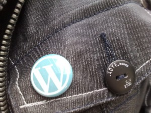 A closeup of a WordPress button pinned to a jacket.