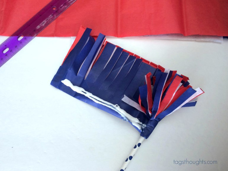 Red, white and blue tissue paper wrapped around a white & blue striped straw.