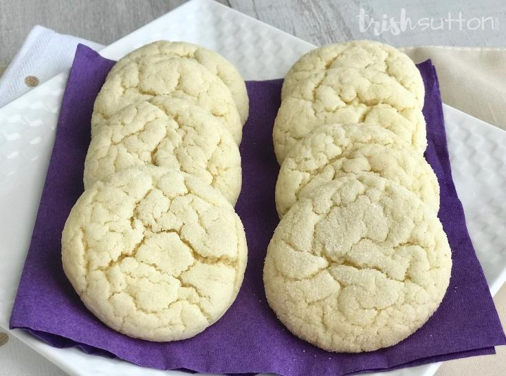 8 sugar cookies on a purple napkin displayed on a white plate