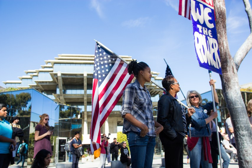 """Lecturer Nan Renner holds a sign: """"We the people. We the power."""" (Curtis Yee / The Triton)"""
