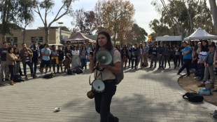 Sam Mitchell, a member of the Yaqui Tribe and UCSD Theatre and Dance Ph.D., led the group to Revelle Plaza. (Gabriel Schneider / The Triton)
