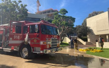 Photo of firefighters and a fire truck outside the Media and Communications building at UC San Diego.