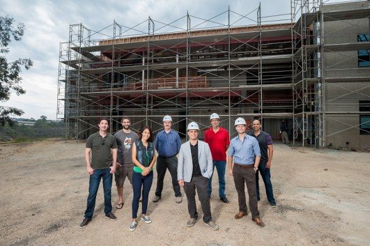 (l to r) David Tamjidi, '03, M.S.'05; Nicolas Fusseder; Jenna Bevilacqua; UC San Diego professor Gary Gillespie; iboss co-founder Paul Martini, '01; Philip Weinroth, '88; iboss co-founder Peter Martini; and Eric Soliz,'01 outside the new iboss location during construction, taken June 30. The space is set to open September 2015, overlooking UC San Diego. (Photo by Xavier Bailey)