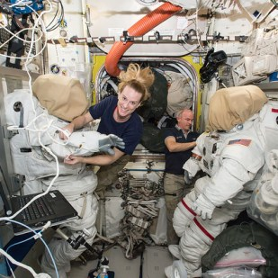 Expedition 48 crew members Kate Rubins (left) and Jeff Williams (right) of NASA outfit spacesuits inside of the Quest airlock aboard the International Space Station. Rubins and Williams will conduct a spacewalk in August 2016 to install the first International Docking Adapter, the new docking port that will enable the future arrival of U.S. commercial crew spacecraft.
