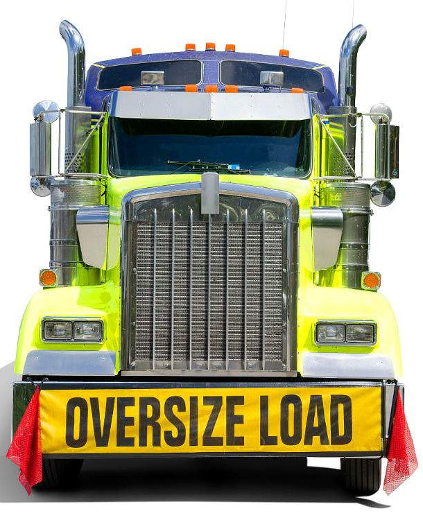 "Image of the front face of a semi truck, green incolor with a banner that reads ""oversized load"""