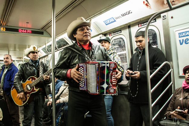 A mariachi band performs on a 4 train subway car