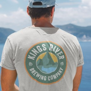 Image of King's River Brewery logo on t-shirt worn by a man overlooking a harbor.