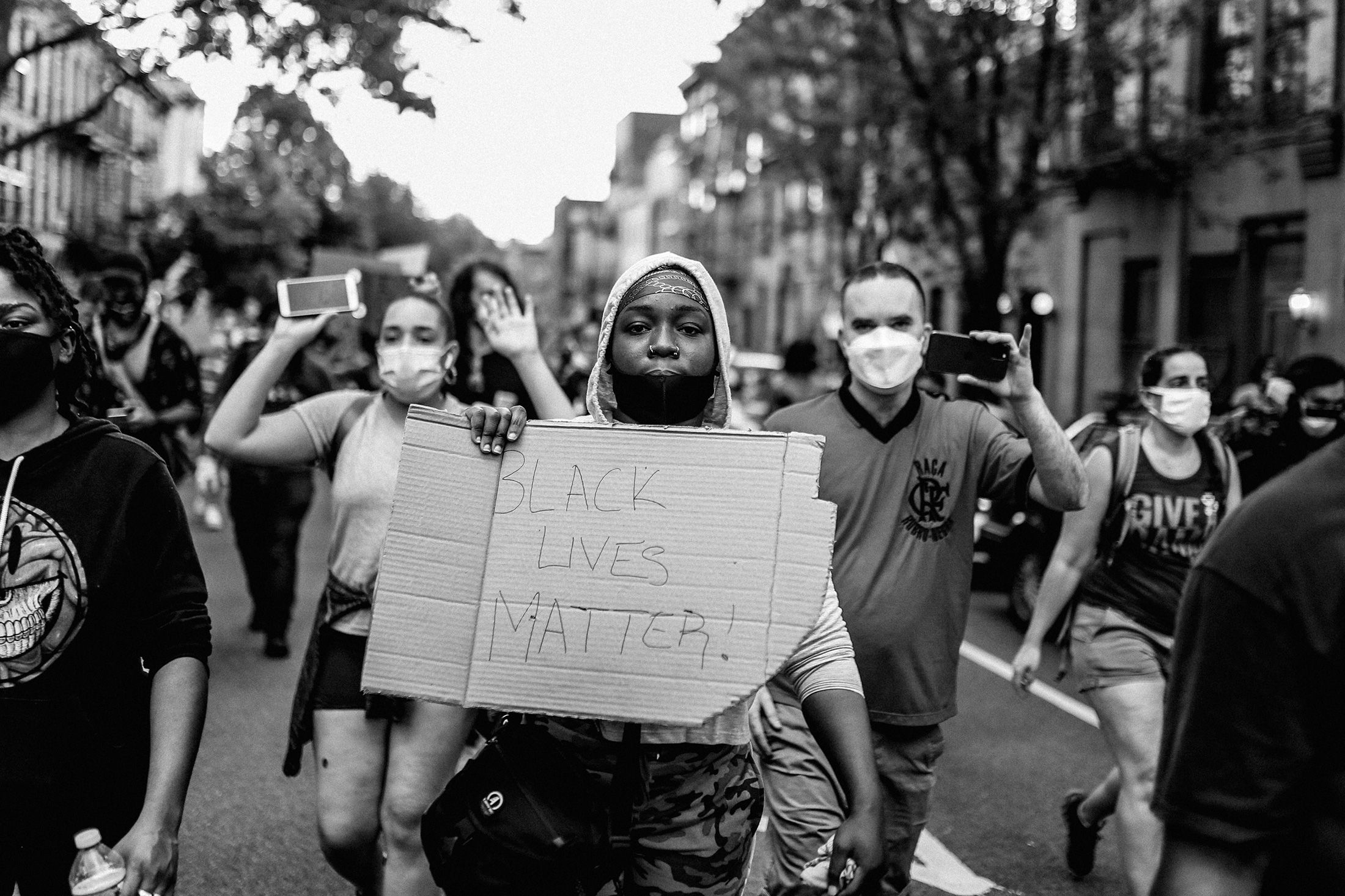 Young woman with Black Lives Matter sign marches at the front of a crowd on May 30 in Downtown Brooklyn, NY. PHOTO: FLO NGALA