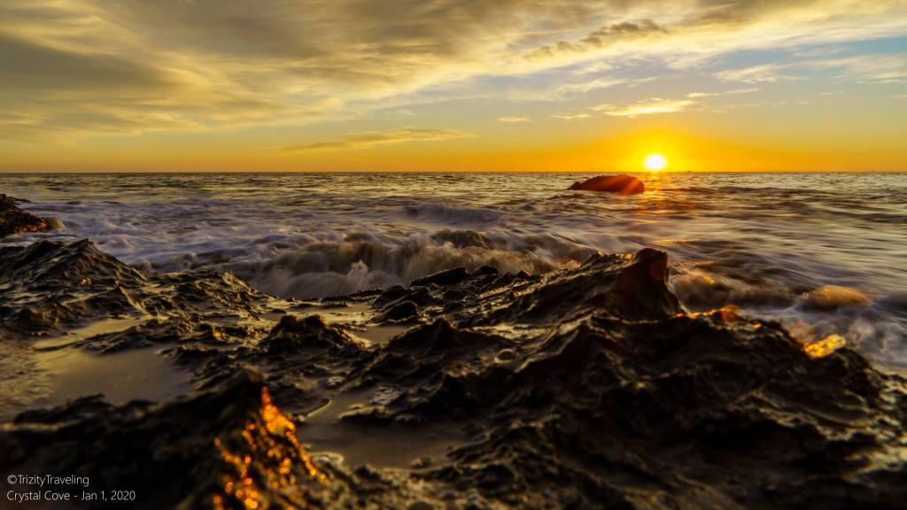vivid sunset color on the beach with waves breaking on the rocks