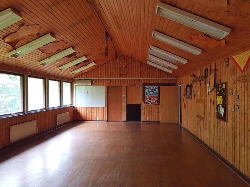 Ett stort långsmalt rum med träpanel på väggar och tak. Längs vänstra väggen är en rad fönster. På högra väggen sitter olika minnessaker från scoutarrangemang.