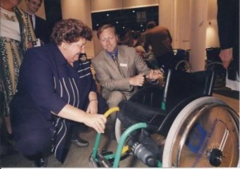 Staatstsecretaris Erica Terpsta  bekijkt samen met Chris Gras de speciaal gemaakte rolstoel voor onze lopers.