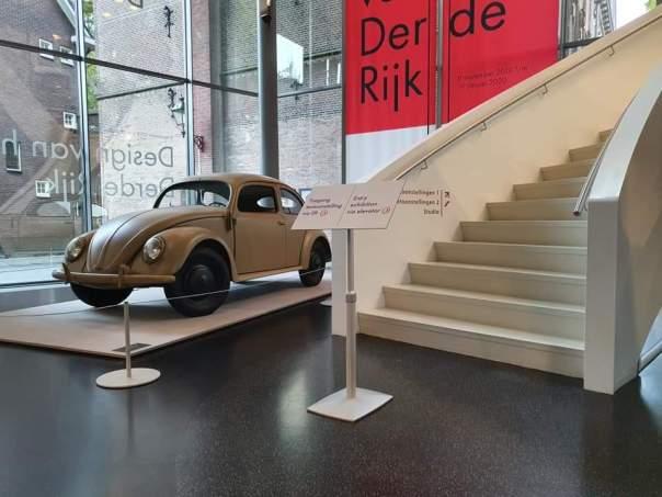 De Volkswagen bedacht door Hitler naast de trap van het designmuseum.