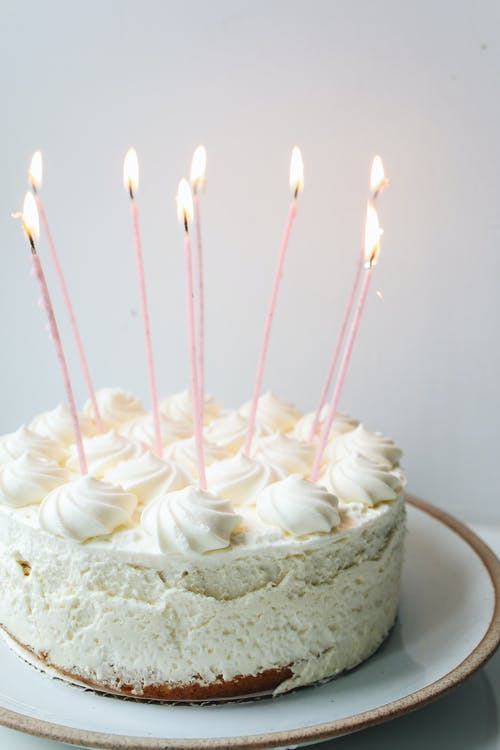 CREAMY, LUCIOUS BIRTHDAY CAKE WITH WHITE ICING AND SEVERL LONG LIT CANDLES