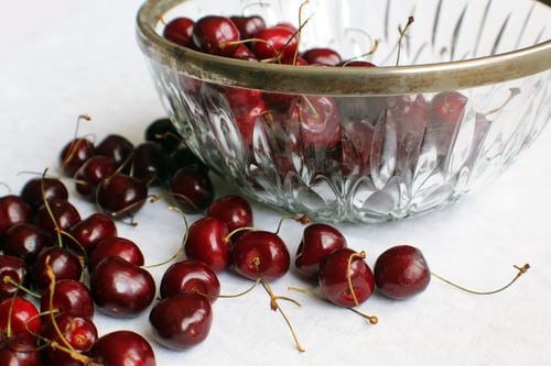 A BOWL OF FRESH BLACK CHERRIES WITH SOME ON THE WHITE TABLE OUTSIDE THE GLASS BOWL.