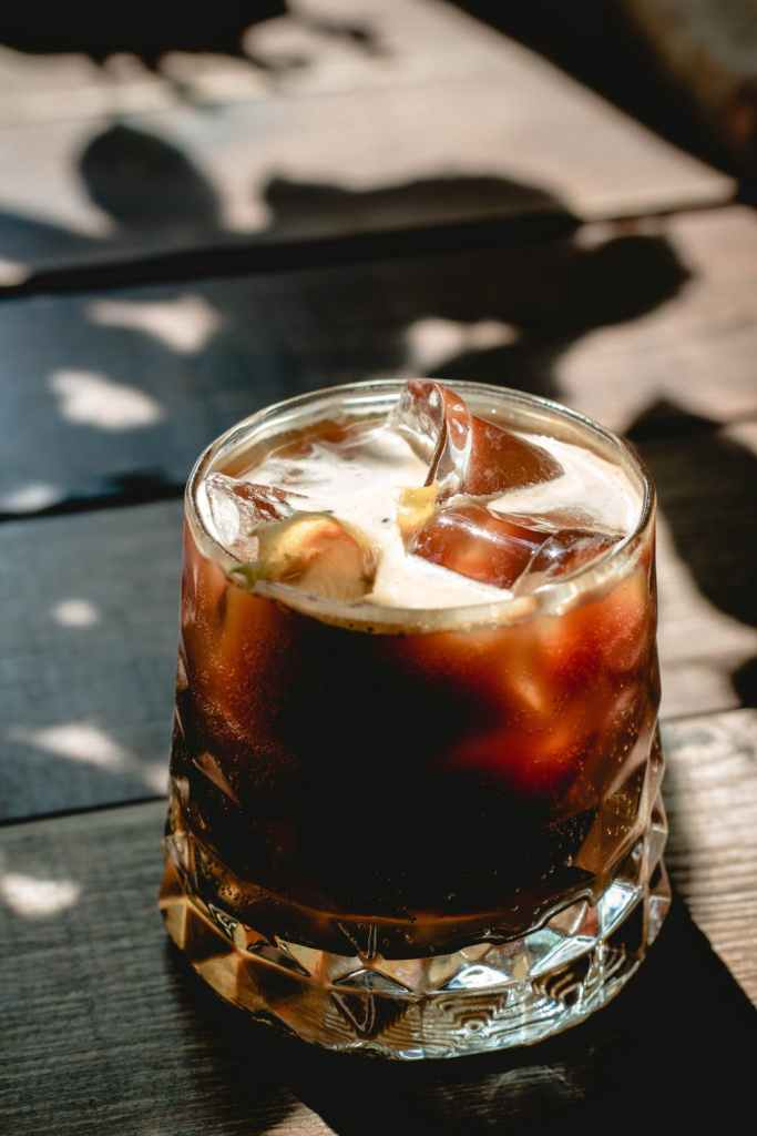 A SMALL GALSS FILLED WITH ICE AND COLA ON PICNIC TABLE COVERD IN THE SHADE OF TREE BRANCHES