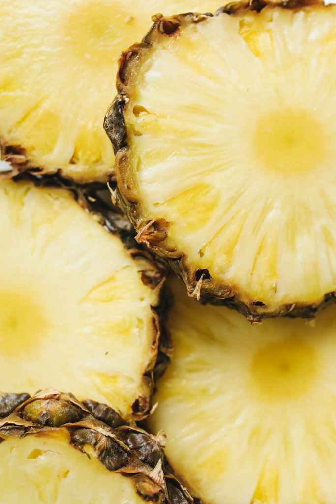 BRIGHT YELLOW SLICES OF FRESH PINEAPPLE WITH RINDS, STACKED TO FILL THE FRAME