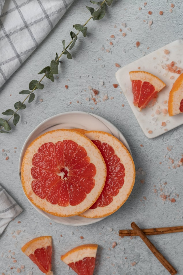 SLICES AND WEDGES OF FRESH PINK GRAPEFRUIT ON WHITE PLATES OF VARYING SHAPES, WITH A CLOTH CROSSHATCHED NAPKIN IN THE UPPER LEFT HAD CORNER, THERE IS SOME GREENERY SCATTERED AROUND