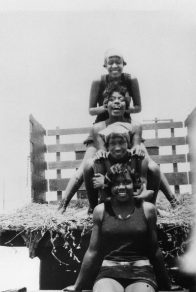 Caption reads: ''Women in bathing suits stack on top of each other in the back of a truck on a hayride to Manhattan Beach (Bruce's Beach). Top to bottom, Susie Thorton, Grace Williams, Mary Mingleton, Grace Harris,'' ca. 1925 | Shades of L.A. Collection, Los Angeles Public Library