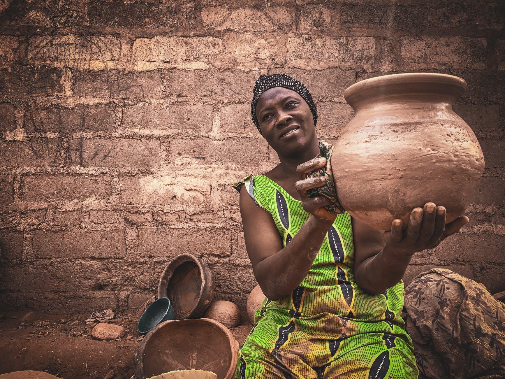 african woman showing handicraft earthenware in local workshop