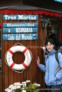 ARANCHA JUNTO A UN CARTEL DE USHUAIA EN EL PARQUE NACIONAL DE TIERRA DE FUEGO