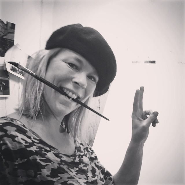 Konstnären Helena Trovaj med basker har en pensel i munnen