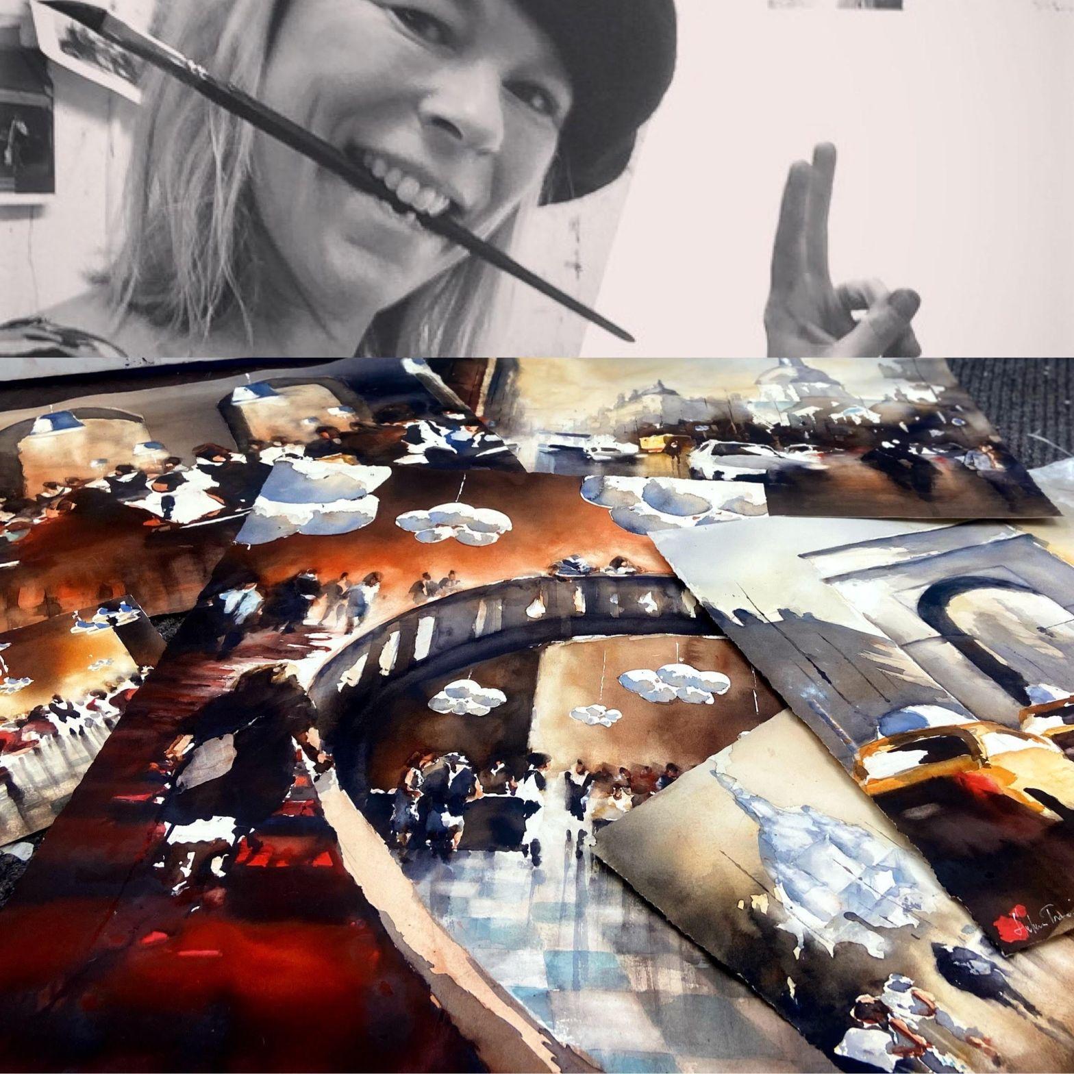 Konstnär står med basker och pensel i munnen vid sina akvarellmålningar