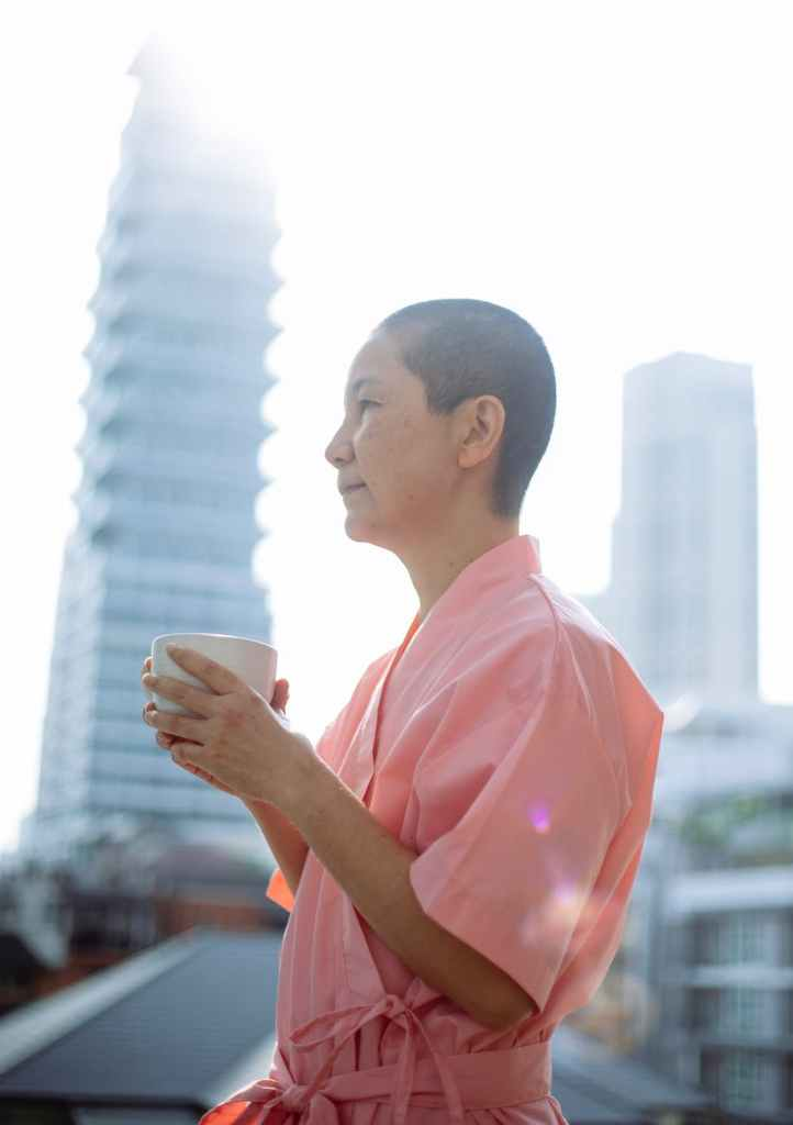 sick asian woman with hot cup of tea in morning