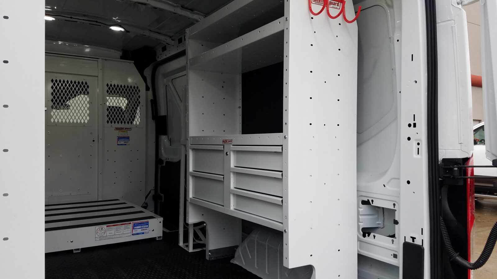 White shelves with white drawers inside a vehicle