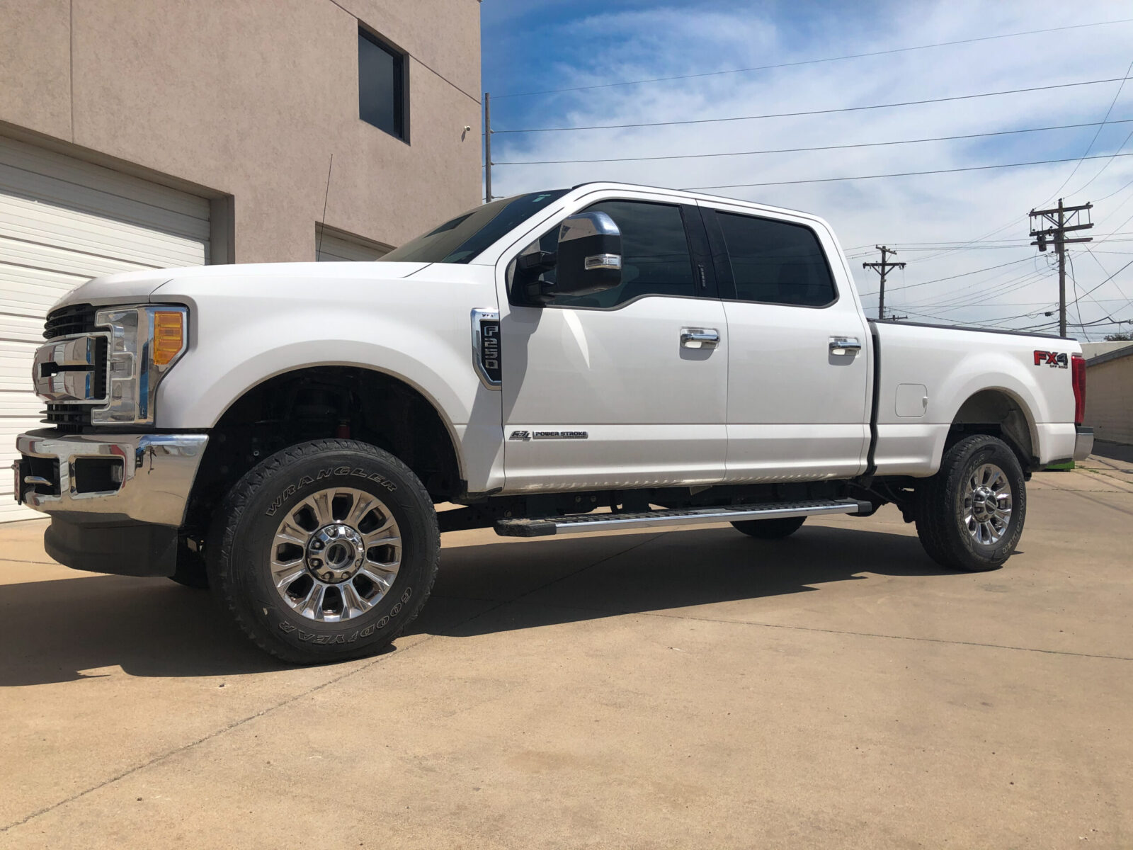 White truck parked outside on concrete pavement, sideview