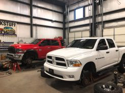 White truck and red truck parked inside shop