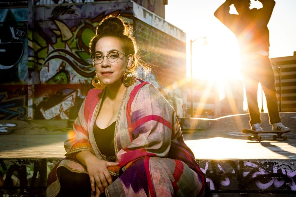Trudi Lebron sits on steps with sunset in the background