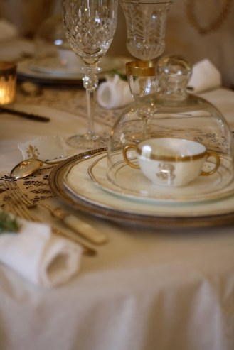 An antique monogramed soup bowl sits under a glass dome before the meal.