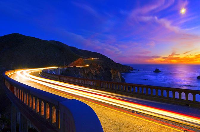 Ponte da Highway 1, já ilumida, vista ao anoitecer.