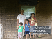 The family in front of their old mud hut