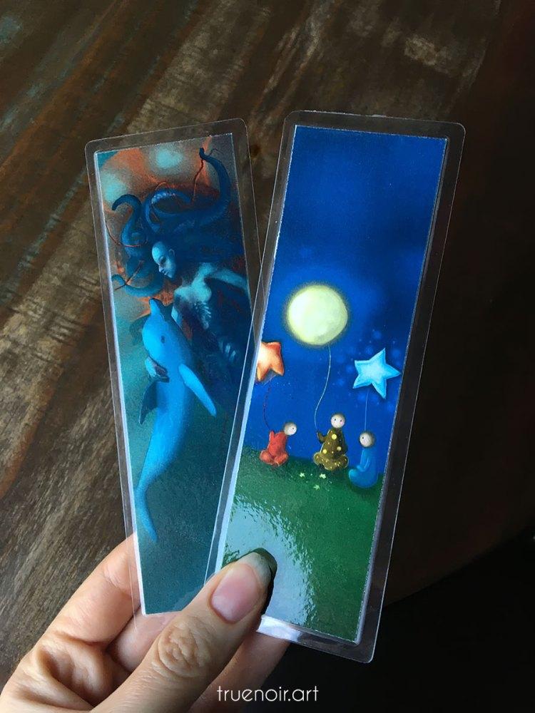 A couple of laminated bookmarks with art by Oksana Ossipov