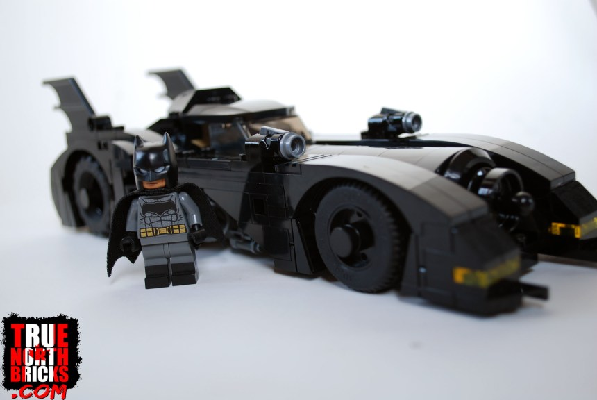 Batman Minifigure next to the Batmobile.